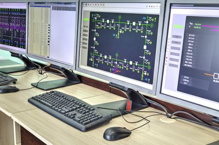 tablero de control: Computadoras y monitores con diagrama esquemático para supervisión, control y adquisición de datos en la moderna sala de control eléctrico Foto de archivo