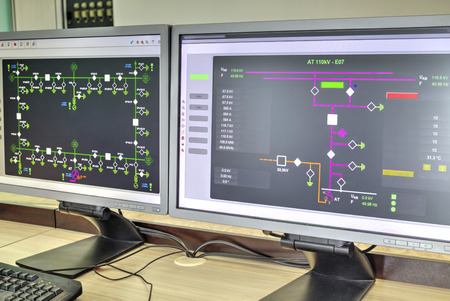 Computers and monitors with schematic diagram for supervisory, control and data acquisition in modern electrical control room Stockfoto