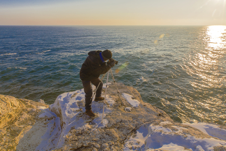 natural ice pastime: Photographer on the rocks taking beautiful landscape pictures Stock Photo