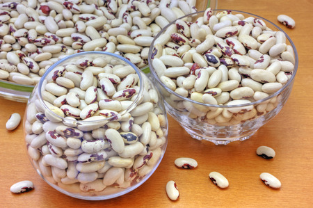 haricot: Colorful haricot beans in glass bowls on wooden background