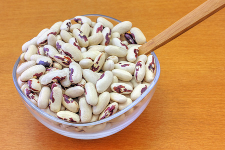 haricot: Colorful haricot beans in glass bowl on wooden background