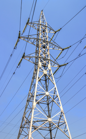 over voltage: High voltage electrical overhead lines on blue sky Stock Photo