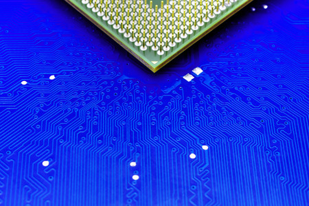 Technological background with blue computer motherboard and central processing unit closeup
