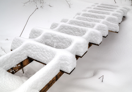 clear path: Wooden bridge covered with snow in winter Stock Photo