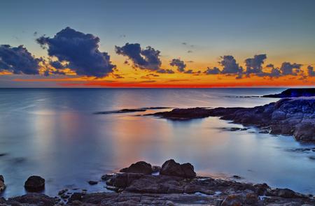 Beautiful sunrise on rocky shore and dramatic sky clouds 免版税图像