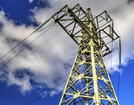 High voltage electrical overhead line on blue sky Stock Photo