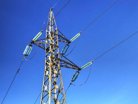 A pilon of overhead power line on blue sky