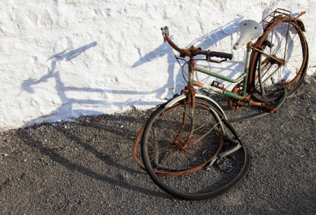 parked bicycles: An old abandoned bicycle and a white wall Stock Photo