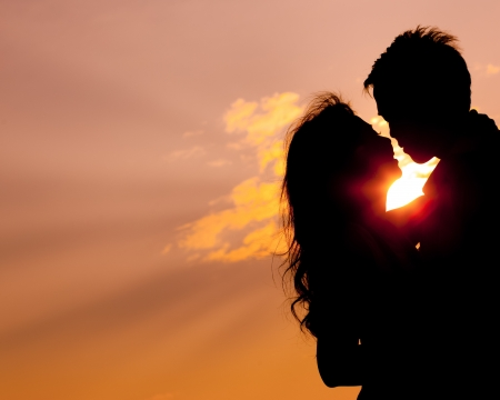 Romantic lovers hugging at twlilight with sunset in background photo