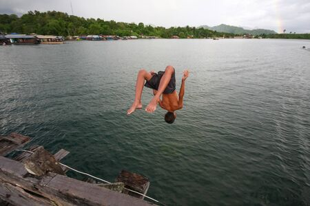 A boy flipping into the scary dark and deep river Stock Photo - 17472944