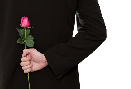hombre en traje celebración de una rosa rosa en la espalda Foto de archivo