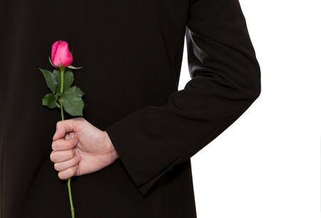 gift behind back: man in suit holding a pink rose in his back Stock Photo