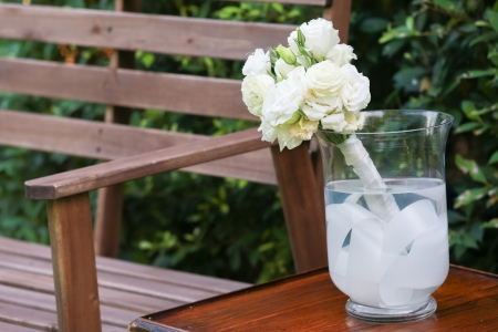 White roses in a glass vase and a wood bench photo