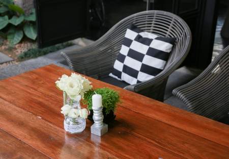 White roses in a glass vase on a wood table and chairs Stock Photo - 18223427
