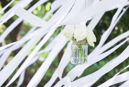 White roses in a glass vase with white ribbons in background