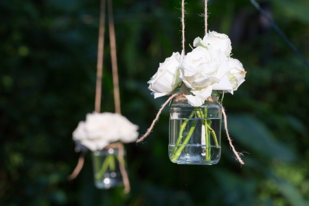 White roses in a glass vase hung in a wedding party photo