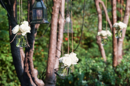 White roses in a glass vase hung in a wedding party