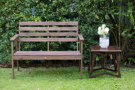 Wood bench decorated with white roses in a grass vase Stock Photo - 18223436