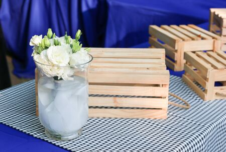 Dinning table decorated with white roses in a glass vase and wooden storage boxes Stock Photo - 18223392