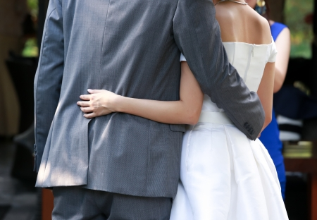 Newlywed put their arms around each others waist photo