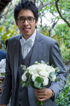 Groom holding beautiful white rose for the bride photo