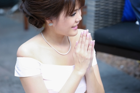 A beautiful young lady greeting in Thai culture style photo