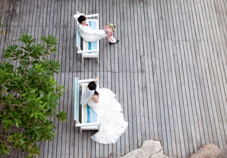 In love bride and groom are relaxing on the bench