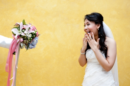 offered: A young bride in surprise with an offered beautiful bouquet