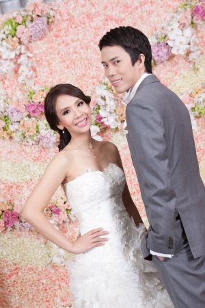 Newlywed bride and groom posing with flower decoration in background