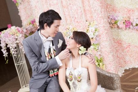 Newlywed Braut und Bräutigam posieren mit Thai-Stil Kranz und Blumenschmuck im Hintergrund