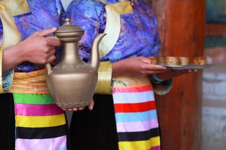 Donne tibetane che servono il tradizionale tè del latte di stile, Shangri-La, Cina Archivio Fotografico - 18540149