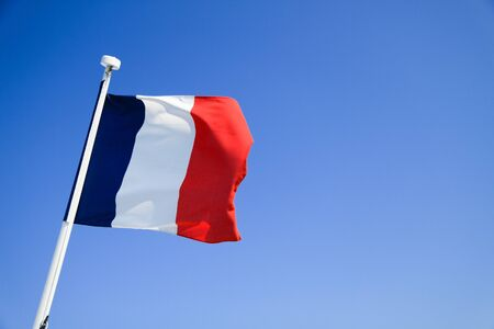 France flag waving with clear blue sky in background photo