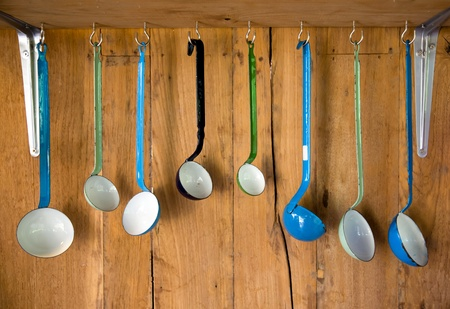 blue white kitchen: Variety of vintage enamel kitchen spoon with wooden background