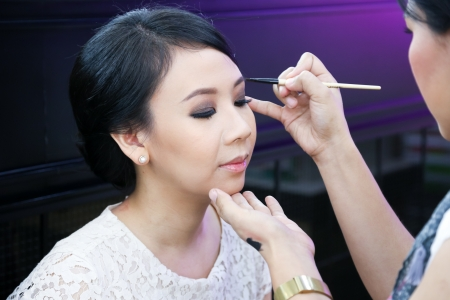 artist's model: Make-up artist applying cosmetics on a beautiful young asian lady