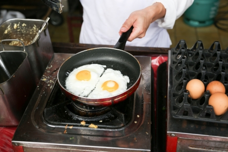 sunnyside: A chef is cooking sunny-side up eggs Stock Photo
