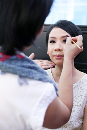 Make-up artist applying cosmetics on a beautiful young asian lady photo