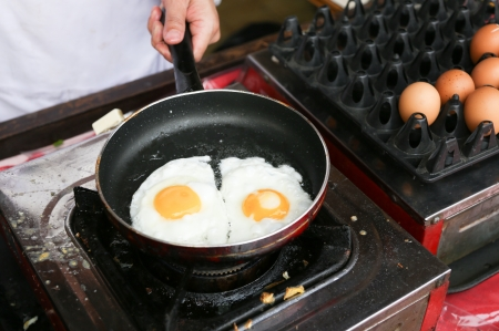 sunny side up: A chef is cooking sunny-side up eggs Stock Photo
