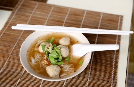 Meat balls noodle in a white bowl with chopsticks photo