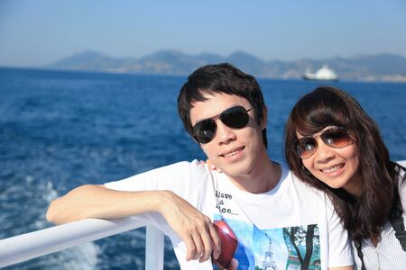 Happy asian couple on a sailing boat photo