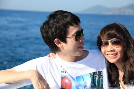 Happy asian couple on a sailing boat Stock Photo
