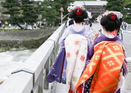 Two geisha walking on a bridge in Arashiyama, Japan