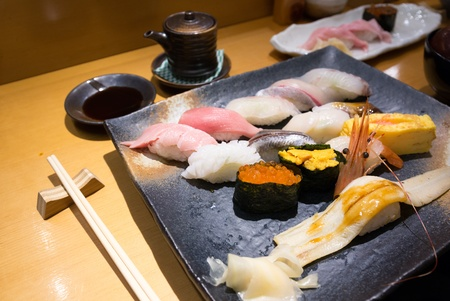 Fresh sushi on a black plate with chopsticks Stock Photo - 19600561