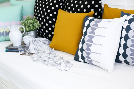 Colorful pillows on a sofa with white brick wall in background Archivio Fotografico