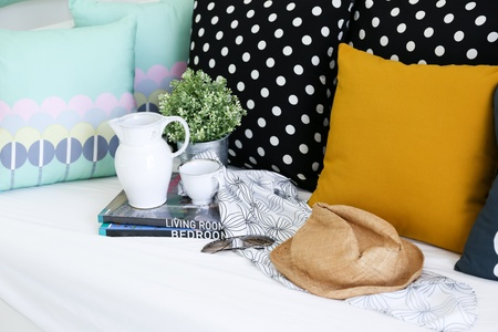 Jar, coffee cup and books with colorful pillows in background