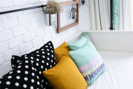 Colorful pillows on a sofa with white brick wall in background Stock Photo