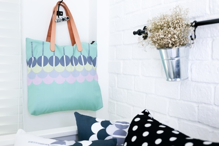 white room: Hand bag hung on the white brick wall with colorful pillows