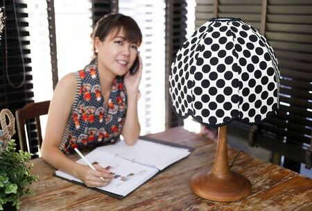 intentionally: Vintage polka dot lamp with intentionally out of focus working woman in background