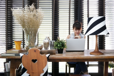 asian working woman: Young asian working woman is using a laptop with vintage decoration Stock Photo