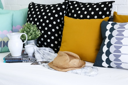 Colorful pillows on a sofa with white brick wall in background photo