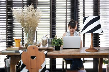 Young asian working woman is using a laptop with vintage decoration photo